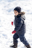 Cute boy playing with snow in the winter park Royalty Free Stock Photo