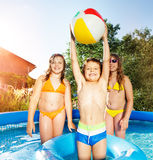 Cute boy playing in swimming pool with two girls Stock Photos