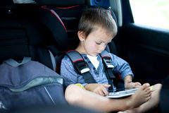 Cute boy, playing on tablet in the car Royalty Free Stock Photo