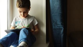 Cute Boy Playing The Tablet PC And Sitting On A Windowsill In The Room stock video footage