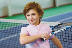 Cute boy playing tennis and posing in court indoor Royalty Free Stock Photos