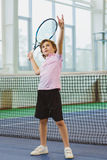 Cute boy playing tennis and posing in court indoor Stock Images