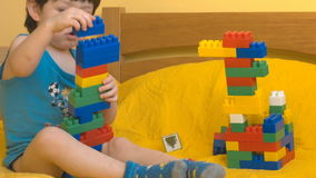 Cute boy playing with toy blocks stock video footage