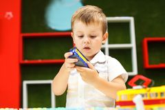 Cute boy playing with tram. Little boy playing with car toy. royalty free stock images