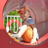 Cute boy playing in tunnel on playground Royalty Free Stock Image