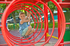 Cute boy playing in tunnel on playground Stock Photos