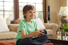 Cute boy playing video games. Sitting on the sofa at home Stock Photos