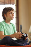 Cute boy playing video games. Sitting on the sofa at home Stock Image
