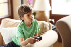 Cute boy playing video games. Sitting on the sofa at home Royalty Free Stock Photos
