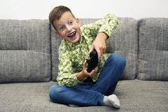 Cute boy playing video games at home. Cute boy playing video games on laptop with joystick sitting on sofa at home Royalty Free Stock Photos