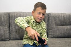 Cute boy playing video games at home. Cute boy playing video games on laptop with joystick sitting on sofa at home Royalty Free Stock Image