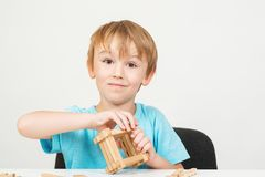 Cute boy playing with wooden blocks, isolated on white background. Education. Studio shot. Back to school concept. Happy childhood royalty free stock photos