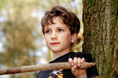 Cute boy playing in the woods. Portrait of cute boy in the woods Stock Image
