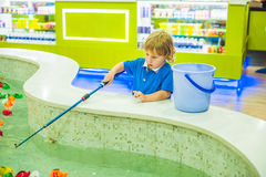 Cute boy in the playroom fishing. The development of fine motor concept. Creativity Game concept Royalty Free Stock Photography