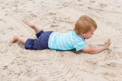 Cute boy plays on the beach Royalty Free Stock Image