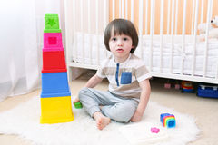 Cute boy plays educational toy at home. Cute 2 years boy plays educational toy at home Royalty Free Stock Image