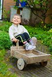 Cute boy plays with toy tools in the garden. 3 years old cute boy plays with toy tools in the garden. Vertical view Royalty Free Stock Photos