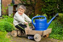 Cute boy plays with toy tools in the garden. 3 years old cute boy plays with toy tools in the garden Royalty Free Stock Images