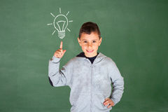 Cute boy pointing up to a light bulb Royalty Free Stock Photography