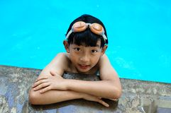Cute Boy at the Poolside. An Asian boy takes a poolside break at a swimming pool Stock Images