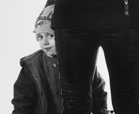 Cute boy portrait hiding. Cute boy hiding behind mother.toned picture stock photography
