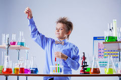 Cute boy posing with variety of reagents in lab Stock Image