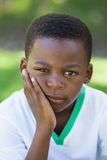 Cute boy pouting at the camera in the park Royalty Free Stock Photos