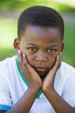 Cute boy pouting at the camera in the park Stock Images
