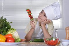 Cute boy preparing. Vegetarian meals in the kitchen Stock Images