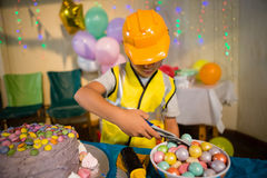 Cute boy pretending to be a worker. While decorating birthday cake Stock Photo