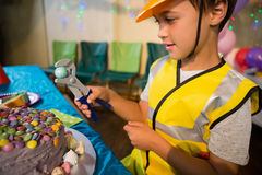 Cute boy pretending to be a worker. While decorating birthday cake Royalty Free Stock Images