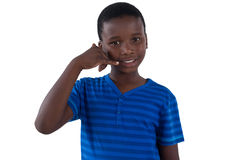 Cute boy pretending to talk on a cell phone. Against white background Stock Photo