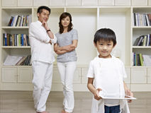Cute boy and proud parents. 6-year old asian boy with proud parents in background Stock Photo