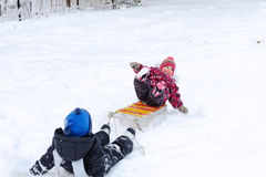 Cute boy pulling his sister on sled Stock Image