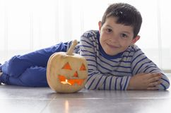 Cute boy with pumpkin in Halloween costume on the floor Royalty Free Stock Photo