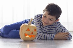 Cute boy with pumpkin in Halloween costume on the floor Royalty Free Stock Photos