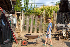 Cute boy pushing a barrow at countryside Royalty Free Stock Photography