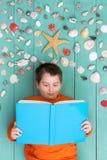Cute boy reading blank book near seashells Royalty Free Stock Photo