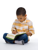 Cute boy reading a book Royalty Free Stock Photos