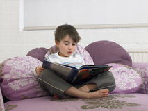 Cute Boy Reading Book On Bed Royalty Free Stock Image