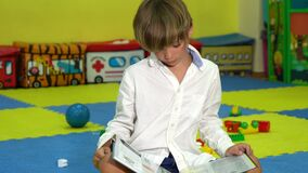 Cute boy reading a book on the floor in the playroom