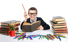 Cute boy reading a book with glasses. Happy child sitting with a book at the table. Royalty Free Stock Photography