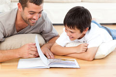 Cute boy reading a book with his father. On the floor at home stock images