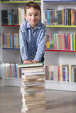 Cute boy reading book in library Stock Photo