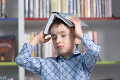 Cute boy reading book in library Stock Image