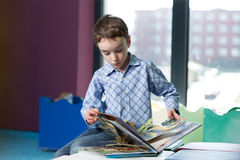 Cute boy reading book in library Royalty Free Stock Photo