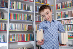 Cute boy reading book in library Royalty Free Stock Photos