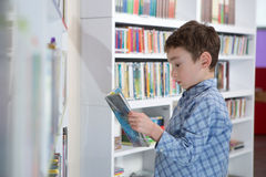 Cute boy reading book in library Stock Photos