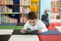 Cute boy reading book in library Stock Images