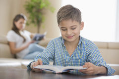 Cute boy reading book with mother in background at home Royalty Free Stock Photography